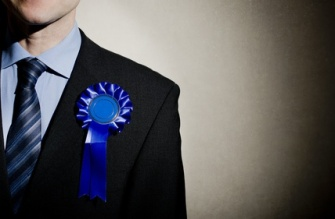 Election candidate with blue rosette.